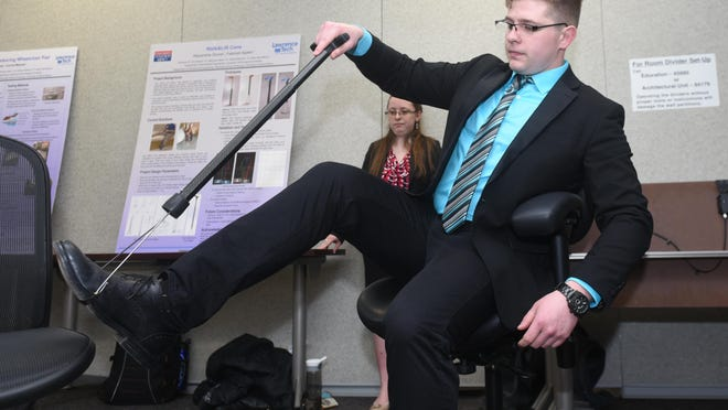 Chris VanOverbeke demonstrates the Lift-Assist Cane, a leg-lift device which quickly converts from a standard cane into a stirrup device, a project by University of Detroit Mercy for their final exams before graduation.