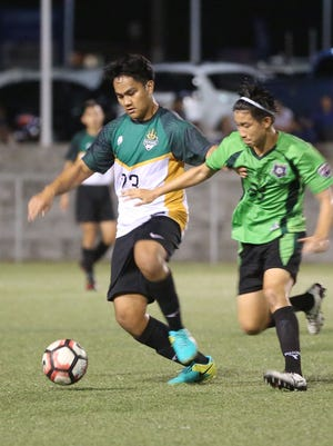 University of Guam Tritons' Jordan Rosario looks to advance the ball facing defensive pressure from Bank of Guam Strykers' Kyle Halehale in a quarterfinal match of the Bank of Guam 10th Annual GFA Cup Friday evening at the Guam Football Association National Training Center. The Strykers advance to the semifinals with a 3-1 win over UOG.