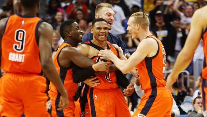Russell Westbrook gets mobbed after sinking a game-winning 3 at the buzzer.