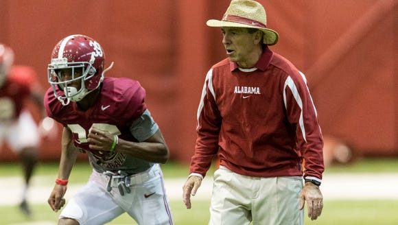 Alabama coach Nick Saban, right, works with his players