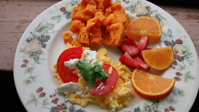 A high-protein breakfast of eggs paired with sweet potatoes and oranges.