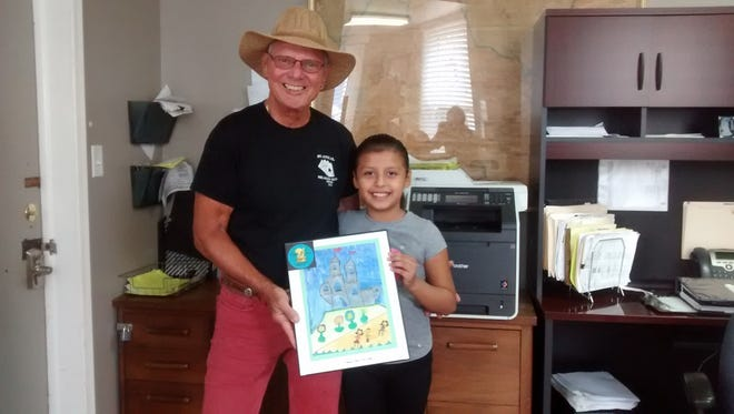 """Bob Thompson of Thompson Realty, the current top donor for Bridgeton Public Library's annual Gold Brush Awards Program, and Evelyn Hernandez, a third grader from Indian Avenue School, show off her artwork. Thompson selected Evelyn's """"A Woman's Home Is Her Castle"""" to display in his office for one year. After that time, the framed artwork will be returned to Evelyn. Through this program, artwork created by Bridgeton students for the library's March student art display becomes available for display throughout the city and local area. Donations by businesses and other entities provide support for the library. For information, call the library at (856) 451-2620 or visit bridgetonlibrary.org."""