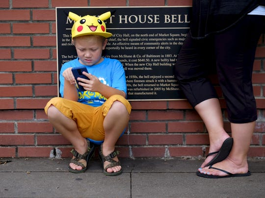 Matthew Trentham,7, plays Pokemon Go along side his mother Nikki in Market Square during the Facebook group, Knoxville Pokemon Go hunt event on Saturday, July 23, 2016.