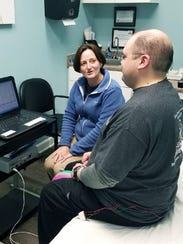 Beth Patterson works with a patient during an evaluation.
