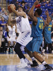 Delaware's Eric Carter (left) looks to the basket past UNC-Wilmington's Cedrick Williams in the second half of the Blue Hens' 70-59 win at the Carpenter Center in 2015.