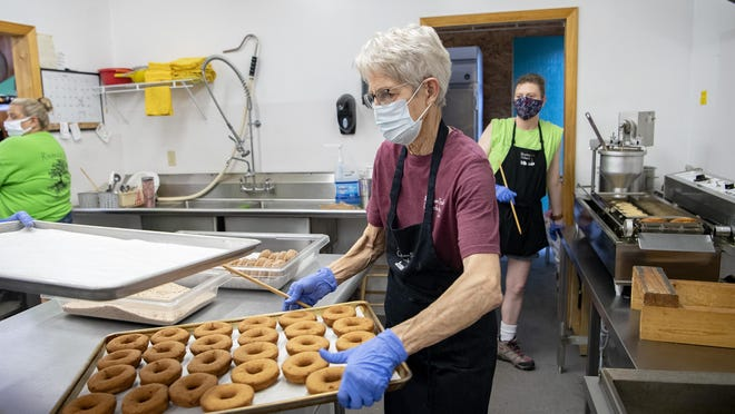 Joan Price, a co-owner of Mountain Fresh Orchards, rearranges fresh doughnuts from the fryer at the orchard Wednesday. Doughnuts are made fresh all day every day and will be one of the many things for sale for visitors during the 2020 North Carolina Apple Festival, which begins Friday.