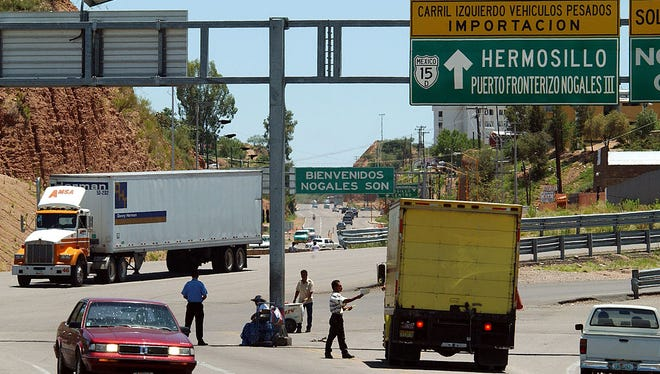 A northbound truck (left) crosses the border to enter the United States from Nogales, Sonora, near Nogales, Arizona.