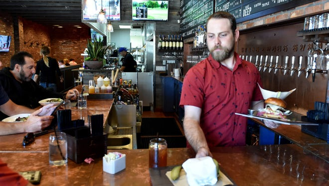 Jake Schumacher, general manager at Finney's Crafthouse and Kitchen in Westlake, serves lunch at the bar during a busy Monday.