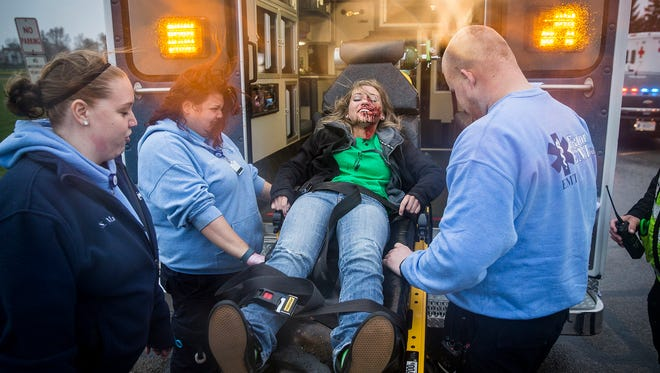 Made up to look like an injured victim of a drunken driving crash, Morgan Riddle is wheeled to an ambulance during the first run through of the annual Living Proof crash re-enactment at Central High School in April 2016.