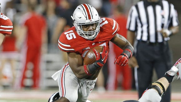 Ohio State University's Ezekiel Elliott makes a bid gain against the University of Cincinnati during the third quarter of their game played at Ohio State in Columbus, Ohio Saturday September 27, 2014. The Enquirer/Gary Landers