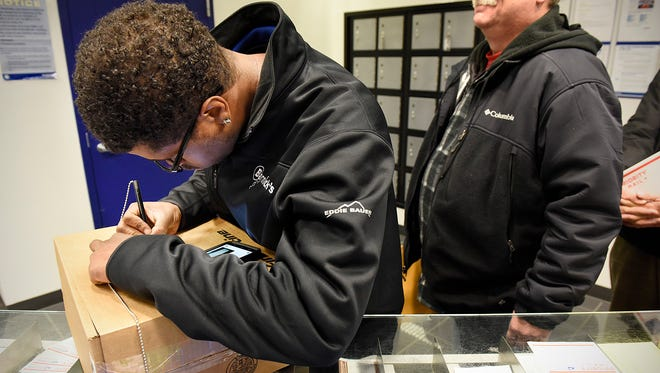 James McKinney, Sauk Rapids, fills out the address label for a box he is sending to his brother in Alaska while waiting in line Monday, Dec. 14 at the U.S. Post Office located on W Division Street.