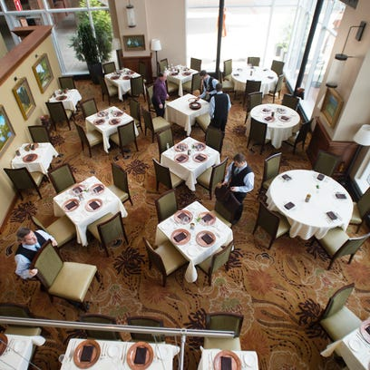Servers set tables in preparation for the dinner crowd at Halls Chophouse in downtown Greenville on Tuesday, April 26, 2016.