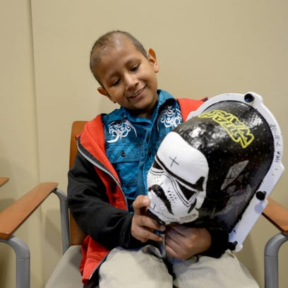 David Romero holds onto a mask that is used during his radiation treatment that was painted by Greenville Health System radiation therapist Jenn Cook.