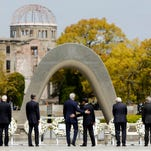 FILE - In this April 11, 2016, file photo, U.S. Secretary of State John Kerry, fourth from left, puts his arm around Japanese Foreign Minister Fumio Kishida after they and fellow G7 foreign ministers laid wreaths at the cenotaph at Hiroshima Peace Memorial Park in Hiroshima, western Japan. U.S. President Barack Obama will travel to Hiroshima in May 2016 in the first visit by a sitting American president to the site where the U.S. dropped an atomic bomb. Obama's visit will bolster his call for denuclearization and honor victims of the bombing that killed 140,000 Japanese on Aug. 6, 1945. The president's visit had long been anticipated.
