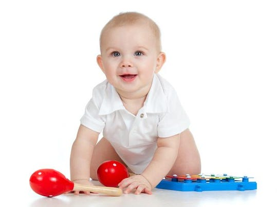 Baby boy with musical toys on white background