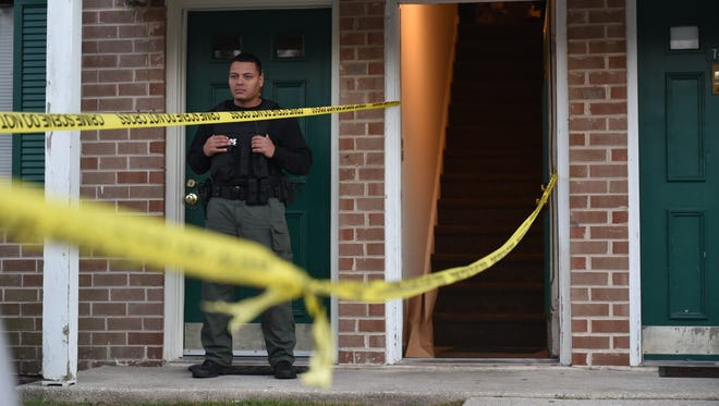 A Vineland police officer stands outside a second-floor unit at the Berkshire apartment complex where two people were found dead Friday.