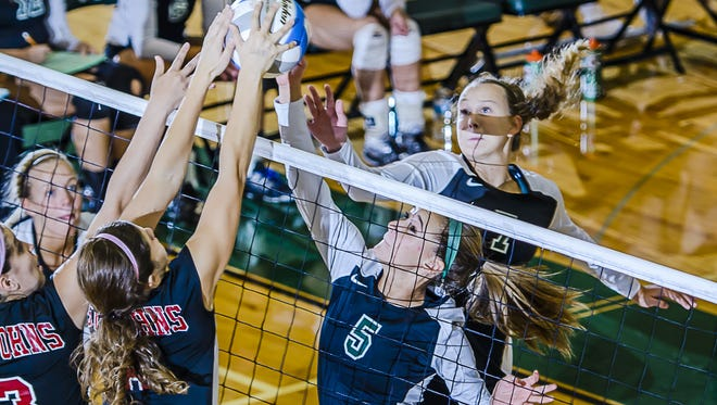 Sarah Schultz (5) of Williamston, shown jousting at the net with Maddy Slamka of St. Johns, helped the Hornets remain in a tie for first place with Williamston by rallying to edge Fowlerville 3-2 on Wednesday night.
