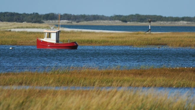 A red boat sits in the high tide off Short Wharf Creek.