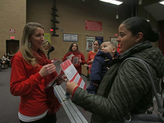 Jen Hansen Teichmann, left, hands out flyers to Jennifer Ramirez before she speaks to the Board of Education advocating for full-day kindergarten during a meeting at North Rockland High School on Jan. 5, 2016.