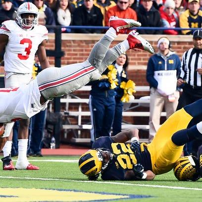Ohio State Buckeyes quarterback J.T. Barrett (16) dives over Michigan Wolverines safety Jarrod Wilson (22)  for a touchdown in the third quarter at Michigan Stadium.