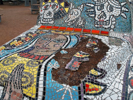 A vintage-era truck covered in mosaic tile sits damaged possibly due to vandalism in San Angelo's Bosque park.