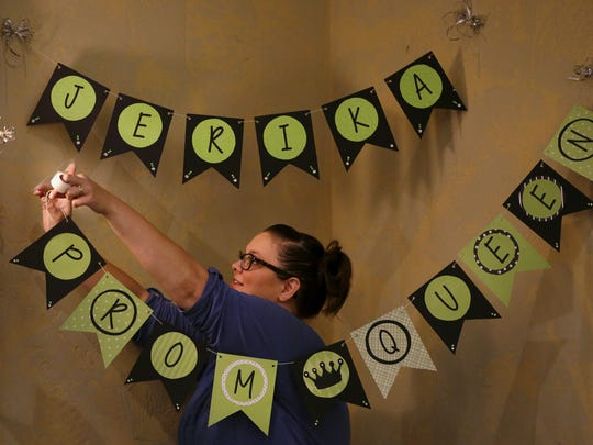 Angela Martinez, one of Jerika Bolen's nurses, hangs a banner Thursday at the Grand Meridian in Appleton in preparation for Jerika's prom on Friday night.
