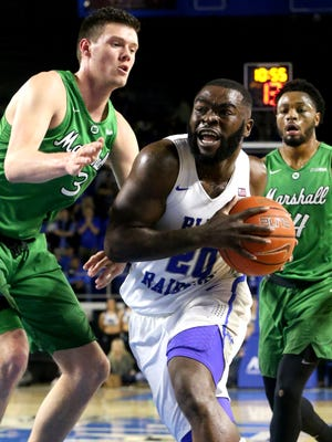 MTSU's Giddy Potts (20) pushes toward the basket as Marshall's Jannon Williams (3) defends him on Saturday.