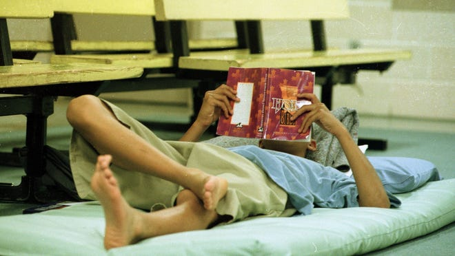 In this file photo, a male juvenile reads a book in the Escambia Regional Juvenile Detention Center.