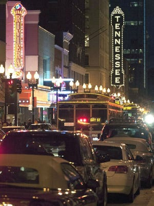 Nightlife traffic moves down Gay Street past the Tennessee Theatre and Regal Riviera Stadium 8 cinema signs in 2013. (J. Miles Cary/News Sentinel)