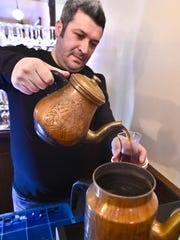 Hasan Oktay, owner of the Istanbul Kebab House in Burlington with his brother Jural (not pictured), pours a cup of tea on Tuesday, February 17, 2015.