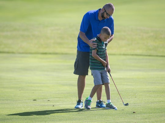 Noah Lennon and his dad work on his golf swing at the Players Club in Yorktown. Noah Lennon is finishing his first year on the Delaware County Special Olympics team as one of the youngest athletes.