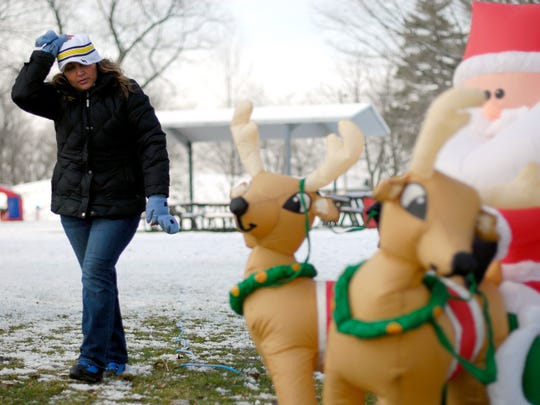 Anita Dado, with Walsh's Party Store in Marysville, sets up her decorations Monday, Nov. 23, at Marysville City Park.