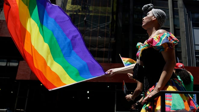 People on a float dance and wave flags during the annual pride parade in New York.