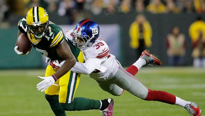 Green Bay Packers receiver Davante Adams is brought down by New York Giants defender Michael Hunter at Lambeau Field.