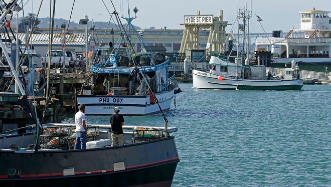 In this Nov. 5, 2015 file photo, fishermen stand on a boat at Fisherman's Wharf in San Francisco.