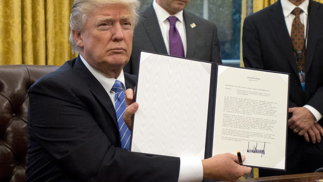 U.S. President Donald Trump shows the Executive Order withdrawing the U.S. from the Trans-Pacific Partnership (TPP) after signing it in the Oval Office of the White House on Monday.
