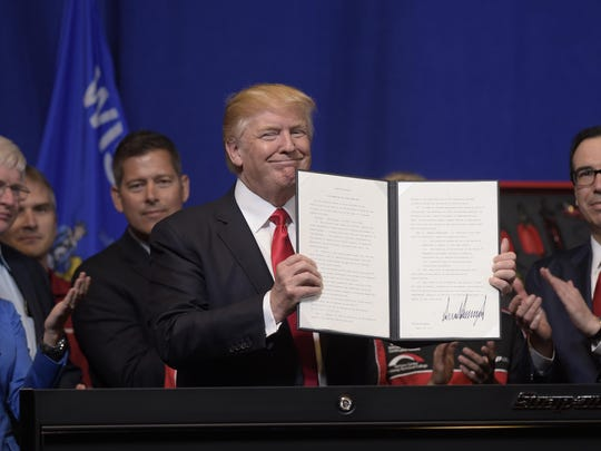 "FILE - In this April 18, 2017 file photo, President Donald Trump holds up the ""Buy American, Hire American"" executive order which he signed during a visit to the headquarters of tool manufacturer Snap-on Inc. in Kenosha, Wis. Immigrants with specialized skills are being denied work visas or seeing applications get caught up in lengthy bureaucratic tangles under federal changes that some consider a contradiction to Trump's promise of a continued pathway to the U.S. for the best and brightest. (AP Photo/Susan Walsh)"