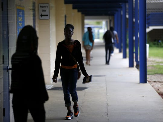 Students walk the outdoor hallways of Rickards High