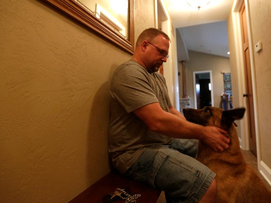 Portage County Sheriff's deputy Dan Wachowiak massages his police dog Baco following the dog's retirement party at the Sheriff's Office, September 7, 2016. Baco may have cancer.