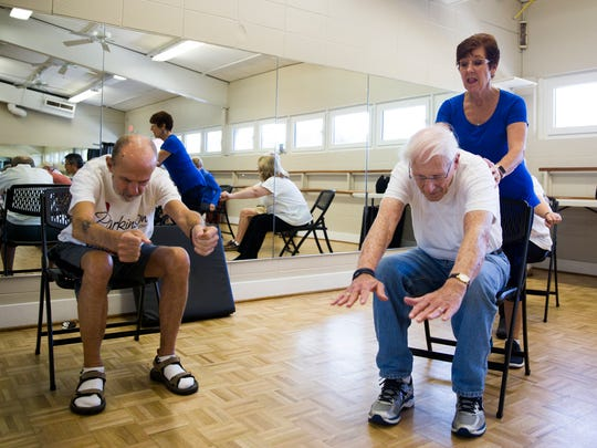 Marjorie Johnston, right, helps Tom Yancy extend his reach as John Merriman stretches to the left during an exercise class for people who have Parkinson's or other issues with mobility on Wednesday, January 4, 2017 in the Fleischmann Park community center. The hour long class featured a series of stretches and balancing exercises.