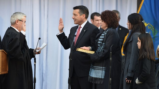 Nevada Governor Brian Sandoval is sworn into office on the steps of the Capitol on Monday Jan. 5, 2014. The first lady Kathleen holds the Bible and daughters Maddy and Marisa stand behind them.