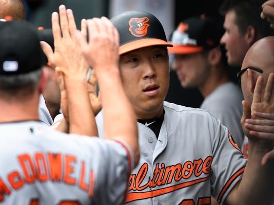 Baltimore Orioles' Hyun Soo Kim, of South Korea, is congratulated in the Orioles dugout after scoring on a double by teammate Caleb Joseph off Minnesota Twins pitcher Kyle Gibson in the first inning of a baseball game, Sunday, July 9, 2017, in Minneapolis. (AP Photo/Tom Olmscheid)