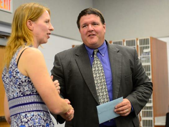 Woodmore School Board President Corinna Bench shakes