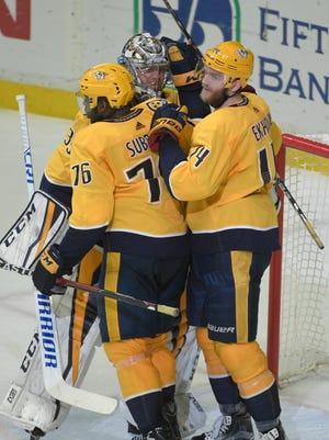 Teammates congratulate Predators goalie Pekka Rinne after getting a shutout against the St. Louis Blues on Sunday at Bridgestone Arena.