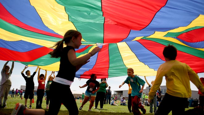 Third-graders at Nickerson Elementary School in Hutchinson, Kan.,  dash under a parachute during the 15th annual Kansas Kids Fitness Day, which offered students a chance to get exercise through fun activities.