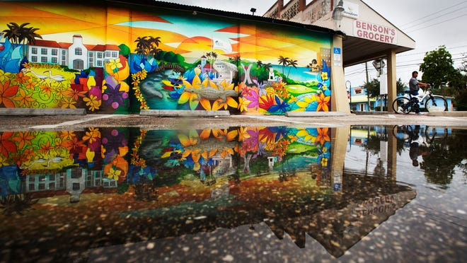 A recently painted mural on the side of Benson's Grocery in Bonita Springs is reflected in a puddle from recent rains.