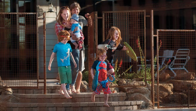 Rachel and Carter Lipton, of Phoenix, with their children (from left) Satchel (6), Abe (6 months), Sol (3) and Adlai (8). The Liptons decided to install a permanent grid-style, rust-colored wrought-iron fence around their pool.