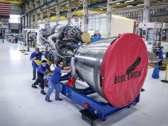 Workers pushing a BE-4 rocket engine across shop floor.