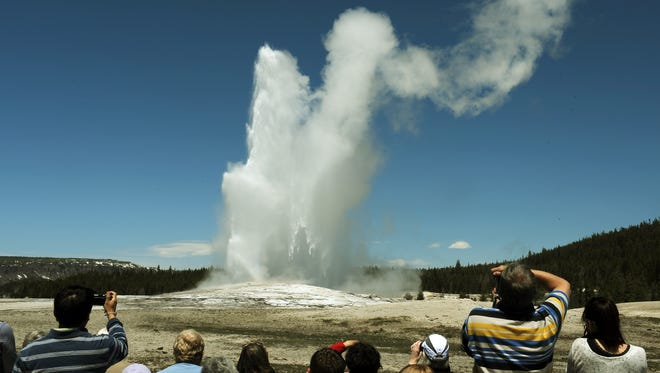 Tourists watch the 'Old Faithful' geyser which erupts on average every 90 minutes in the Yellowstone National Park, Wyoming on June 1, 2011.  Yellowstone National Park, was established by the U.S. Congress and signed into law by President Grant on March 1, 1872. The park is located primarily in the U.S. state of Wyoming, though it also extends into Montana and Idaho and was the first national park in the world. It is known for its wildlife and its many geothermal features, especially the Old Faithful Geyser.        AFP PHOTO/Mark RALSTON (Photo credit should read MARK RALSTON/AFP/Getty Images)