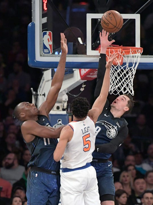 Orlando Magic forward Mario Hezonja (8) goes up to block a shot by New York Knicks guard Courtney Lee (5) as Orlando Magic center Bismack Biyombo, left, helps out during the first quarter of an NBA basketball game Tuesday, April 3, 2018, at Madison Square Garden in New York. (AP Photo/Bill Kostroun)